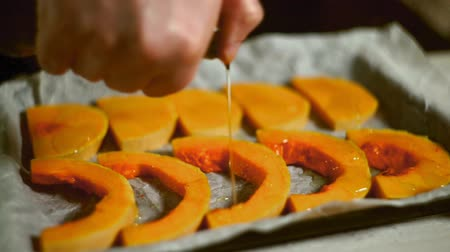 bandeja : Pumpkin pieces pouring olive oil. Close up of chef hand pumpkin sliced pouring oil. Pumpkin dish cooking. Baked vegetables cooking. Raw pumpkin slices olive oil pour Stock Footage