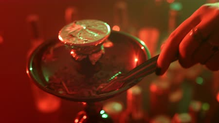 никотин : Female hands take hot charcoal with metal tweezers for hookah. Close up hand put hot coal on bowl of nargile. Coal for hookah smoking is placed on bowl with a falcon. Hot coal for shisha smoking
