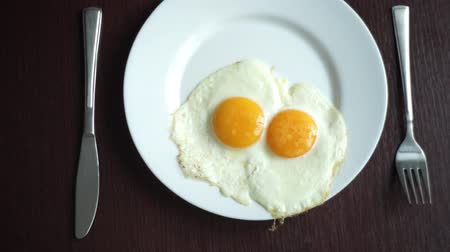çatallar : White plate with fried egg on wooden table. Serving breakfast eggs. Fried eggs on plate. Close up white porcelain plate with breakfast eggs fried. Traditional breakfast on white plate