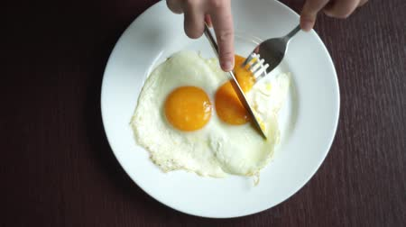 çatallar : Cutting fried eggs with knife and fork on white plate at wooden table. Eating eggs. Traditional breakfast. Eating fried eggs with knife and fork. Top view of fried eggs on white plate