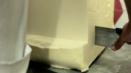 chop up : Butter block cutting. Close up of butter piece cutting with knife. Slicing butter piece. Food production. Big stick of butter cutting. Milk products. Margarine slice cutting