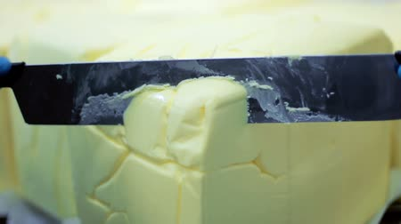 chop up : Cutting food ingredient. Close up of cutting butter block with knife. Ice cream ingredients. Milk products. Knife cutting butter block. Margarine butter cut