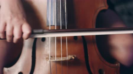 hegedűművész : Woman hand playing violoncello with cello bow. Close up of female hand playing cello with cello bow. Cello playing music background. Female musician playing violoncello Stock mozgókép