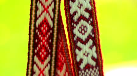 tradição : Red ribbon decoration with white slavic pattern. Slavic amulets with embroidered ethnic print. Traditional ribbons with ethnic white ornament. Close up ethnic bandages with geometric pattern