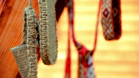 klapki : Wicker vintage bast shoes hanging on street. Traditional old bast shoes and ribbons with ethnic pattern in background. Close up national woven slavic basketry shoes. Slavic country wicker shoes