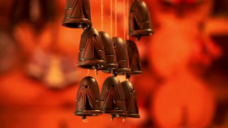tradição : Man hand touching ceramic bells. Ceramic bells pendant chimes wind music on red background. Close up touch clay bells wind music. Ethnic ceramic bells sound wind slowly swinging