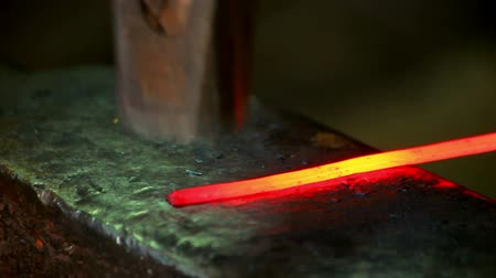 hammered : Smith beating hammer hot iron on anvil in forge. Blacksmith forging red hot metal on anvil. Close up red hot metal on blacksmith anvil. Metal forging. Hot iron on anvil blacksmith Stock Footage