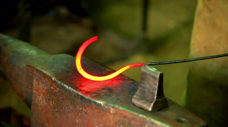 hammered : Smith forming red hot iron in hook on anvil. Blacksmith in forge beats hammer hot metal on anvil. Metal forging. Close up of hot iron on anvil blacksmith. Hot iron on anvil in workshop
