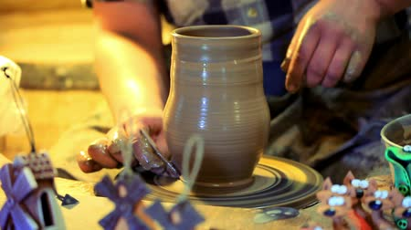 kamenina : Potter making clay vase. Male potter make ceramic dishes. Close up traditional process of making clay dishes on potters wheel. Traditional process making clay pitcher on potter wheel