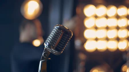 light amplification : Retro microphone on stage. Close up of vintage radio microphone. Silver microphone in retro style. Old microphone on stage against background of stage lighting