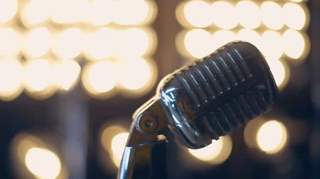 vokální : Retro microphone stage. Close up vintage microphone on stage. Old microphone on light background. Professional microphone on background light