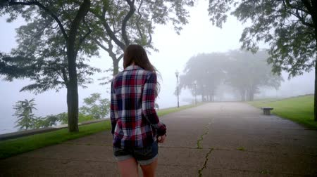 walking back : Young woman walking in park fog. Beautiful brunette woman going in empty park. Walking woman back view. Walking girl in fog trees. Back view of woman in denim shorts walking at park