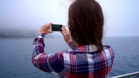 holding steady : Young beautiful woman making mobile photo of modern city fog. Steadyshot of brunette woman making photo of chicago city. Mobile photography. Stock Footage