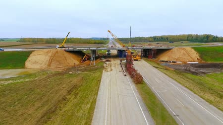 мостовая : Road bridge construction. Aerial view of bridge construction over highway. Drone view of suburban road construction. View from above highway road repair. Building bridges on suburban road