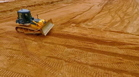 yükleyici : Sand mining industry. Bulldozer machine. Crawler bulldozer moving at sand mine. Mining machinery working at sand quarry. Drone view of mining equipment at industrial sand quarry. Earth mover Stok Video