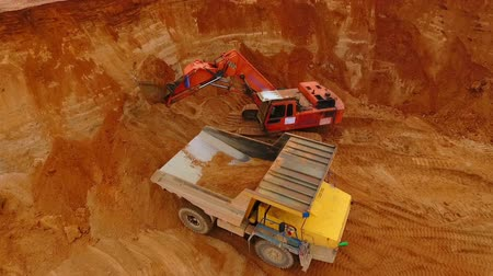 crawler : Excavator pouring sand in mining truck at sand quarry. Aerial view of crawler excavator mining sand at quarry. Drone view of mining machinery working at sand mine. Excavator loading dump truck Stock Footage