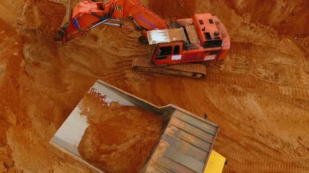 crawler : View from above of mining excavator pouring sand in dumper truck. Crawler excavator mining sand in quarry. Sky view of industrial machinery at sand quarry. Mining industry. Dump truck