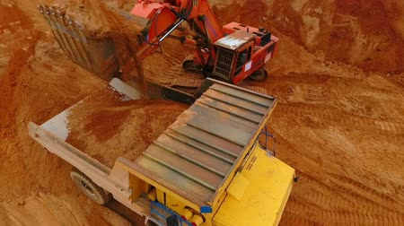 яма : Mining excavator loading sand in dumper truck at sand quarry. Closeup of excavator bucket pouring sand in truck at sand mine. Drone view of mining equipment. Mining industry. Mining machinery