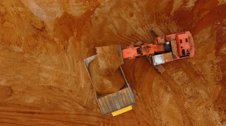 crawler : Top view of excavator pouring sand in dump truck. Aerial view of mining sand process at sand quarry. View from above of mining machinery. Mining industry. Mining equipment working at sand mine Stock Footage