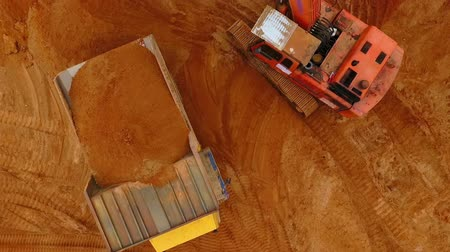 guba : Sand work aerial view. Drone view of mining truck and excavator working at sand quarry. Mining excavator pouring sand in dump truck. Aerial view of mining equipment. Mining machinery at sand mine Stock mozgókép