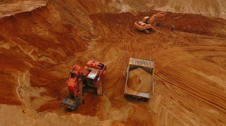 crawler : Aerial view of mining machinery working at sand quarry. Mining excavator pour sand in sand truck. Sky view of mining equipment on sand mine. Mining machines working in sandpit. Construction industry Stock Footage