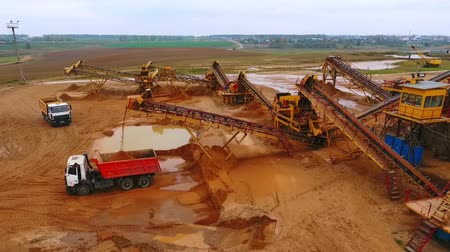 яма : View from above mining conveyor working on sand mine. Mining conveyor pour sand in dumper truck. Mining equipment on industrial park. Aerial view of mining machinery on sand quarry