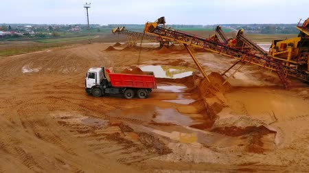 яма : Mining conveyor pour sand in dumper truck. Mining conveyor belt working at sand mine. Mining machinery at industrial park. Mining equipment ot sand quarry. Sand work aerial landscape