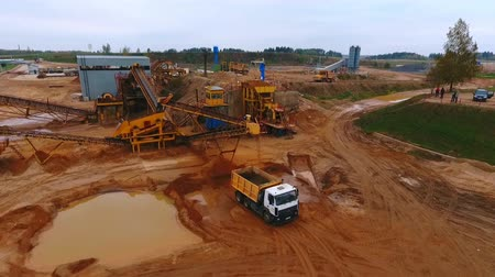 погрузчик : Sand extraction at quarry. Sky view of mining equipment working at industrial area. Mining truck moving at industrial territory sand mine. Mining conveyor pour sand at dumper truck. Aerial view Стоковые видеозаписи