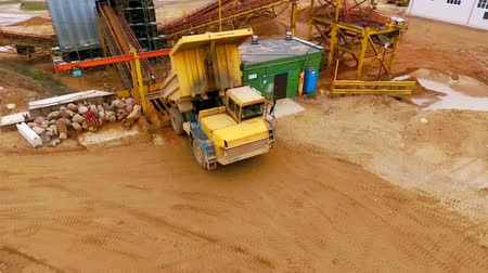 área de trabalho : Dump truck dumping sand to sorting conveyor. Sand sorting process on mining conveyor. Aerial view of mining machinery working at sand quarry. Mining equipment for sorting sand. Mining truck