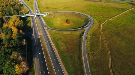 мостовая : Drone view road intersection and cars traffic on highway. Aerial view road junction highway. Car traffic on highway. Cars driving on road circle. Cars driving on country road view from above Стоковые видеозаписи
