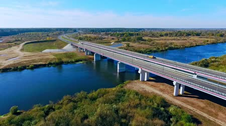 bird's eye view : Aerial bridge landscape. Aerial view highway bridge over river. Cars driving along highway bridge. Aerial highway road over river. Sky view highway on river landscape. Aerial road bridge