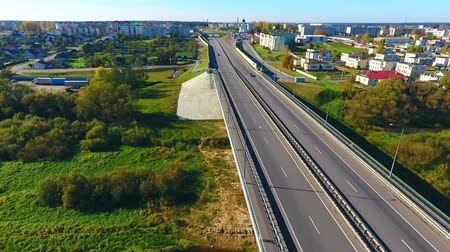 příjezdová cesta : Aerial view of city road over river. Sky view of highway road in city. Drone view of cars driving on highway road at city. Highway road in city landscape. Urban landscape view Dostupné videozáznamy