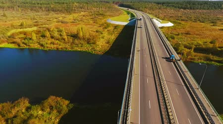 мостовая : Car bridge over river and highway road. Aerial view cars driving over highway bridge landscape. Autumn road view from above. Cars traffic on road river landscape. Highway on autumn background