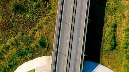 мостовая : Aerial view highway road in green field. Cars driving on suburban road. Highway landscape view. Top view cars and cargo truck moving on highway. Cars driving over highway bridge.