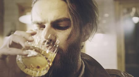 бурбон : Handsome bearded man drinking brandy. Close up of beard man drinking whiskey. Manly man drink glass. Bearded hipster face. Male beard portrait. Drinking man face Стоковые видеозаписи