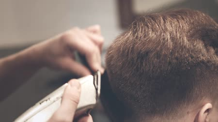 grzebień : Male hairdresser cutting hair. Male hair cut. Close up of barber doing men haircut trimmer in barbershop. Man hair care. Male haircut. Cutting hair with electric razor. Male hairstyle Wideo