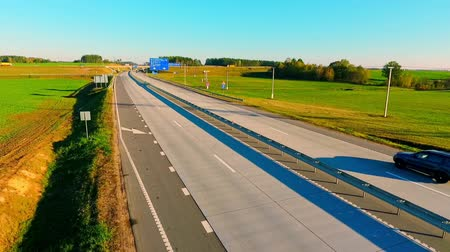 příjezdová cesta : Cars and cargo trucks driving on highway road. Highway sing on country road. Cars traffic on country road. Cars moving on road aerial view. Drone view of highway traffic