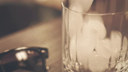 karbonatlı : Hipster drink. Pouring cola in glass with ice. Whisky glass. Whisky cola. Whiskey liquid. Ice drink. Close up of whiskey ice cola drink. Glass ice cubes Stok Video