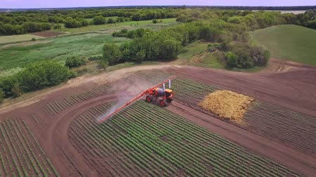 fertilizing : Agricultural sprayer irrigating plant on farming field. Aerial view process watering field. Spraying machine agriculture irrigation. Farming industry. Agriculture watering