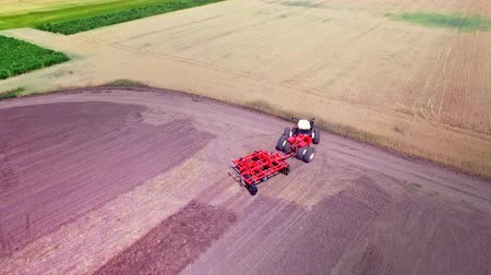 трактор : Agricultural machinery working on agricultural field. Agricultural tractor with trailer plowing on farming field. Sky view process plowing rural field. Agricultural industry. Farming equipment