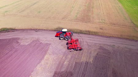 ploughing : Agricultural tractor with trailer ploughing on agricultural field. Farming tractor plowing farming field. Drone view agricultural machinery on farming field. Agricultural industry. Agriculture aerial