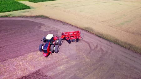 tırmık : Agricultural tractor with trailer for ploughing working on cultivated field. Process plowing agricultural field. Aerial view farming tractor plowing agricultural field. Agricultural technology