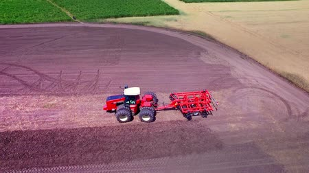 ploughing : Agricultural tractor with trailer for ploughing working on cultivated field. Drone view agricultural vehicle on farming field. Farming tractor plowing agricultural field. Rural farming. Farming aerial