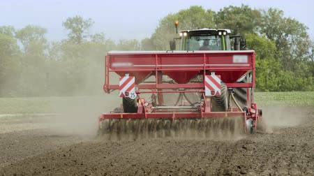 seeder : Farm tractor with trailer seeder sowing on plowed land. Sowing machine working on plowed field