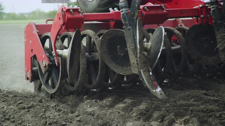 seeder : Blades cultivator and seeder sowing machine working on agricultural field. Agricultural machinery for scattering seeds moving on farmer field