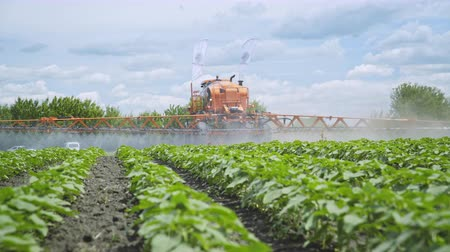 irrigate : Agriculture fertilizer pesticide spraying. Agricultural sprayer watering plant on farming field. Farming agriculture machinery. Fertilizing plants Stock Footage