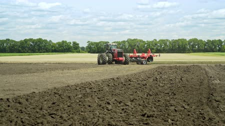 ploughing : Farming tractor moving on agricultural field for plowing land. Agricultural tractor plowing farming field. Agricultural machinery on plowing field Stock Footage