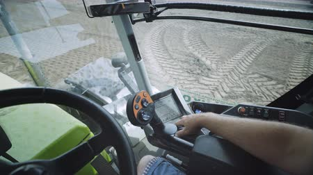 Driver view in tractor cab. Modern agriculture tractor cabine. Tractor driver using touch screen control panel. Rural agriculture vehicle