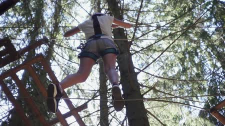 carabine : Young woman in protective equipment for climbing walking on rope on high in extreme park. Extreme sport for active people climbing trees in adventure park