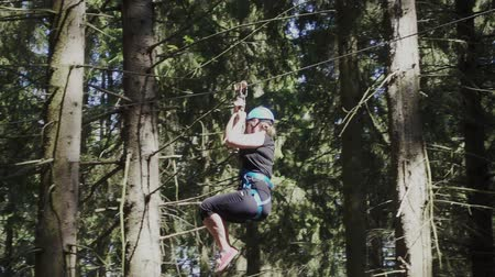 carabine : Young woman in protective helmet and belt moving on rope with carbine on high in extreme park. Extreme descend on rope between trees in climbing park Stock Footage
